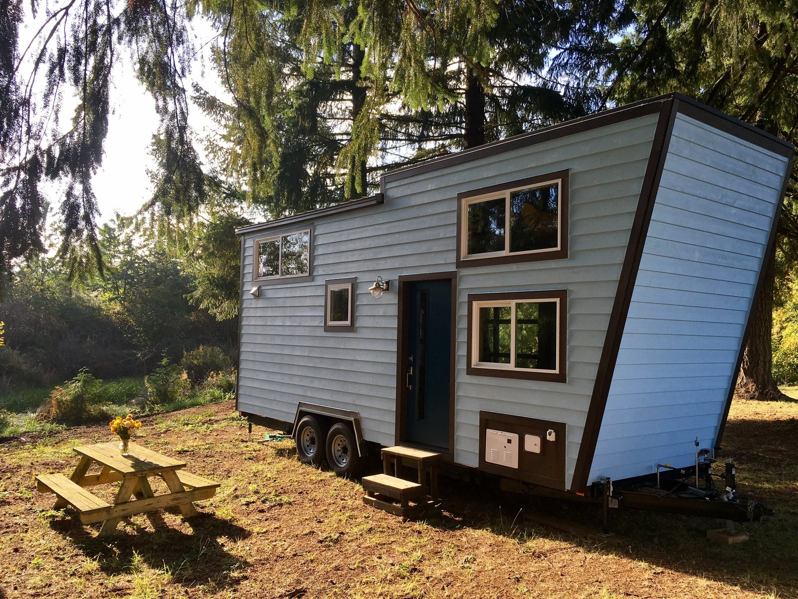 Exterior, Camper, Flat, Tiny Home, and Wood A peek at the back side of the trailer where the front door is located.    Best Exterior Wood Camper Photos from This Tiny Trailer Home Lets Its Owners Climb Up the Wall