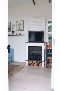Built into the wall near the sofa bed is an electric fireplace with a smart TV above it.