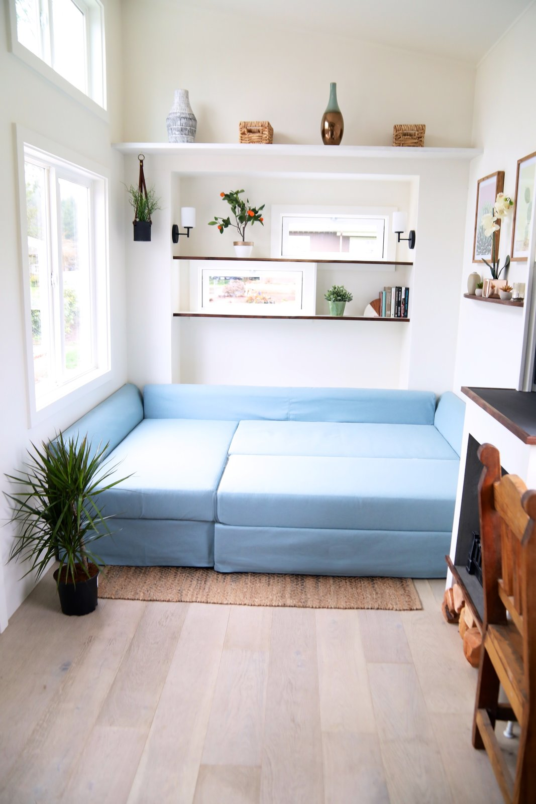 Living Room, Shelves, Wall Lighting, Light Hardwood Floor, Sofa, Rug Floor, and Standard Layout Fireplace A light blue sofa bed was purchased from IKEA.  Photos from This Tiny Trailer Home Boasts Soothing Beach Vibes