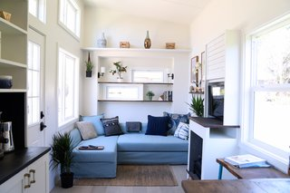 To one side of the entrance door is a large, light blue, chaise lounge-style sofa bed.