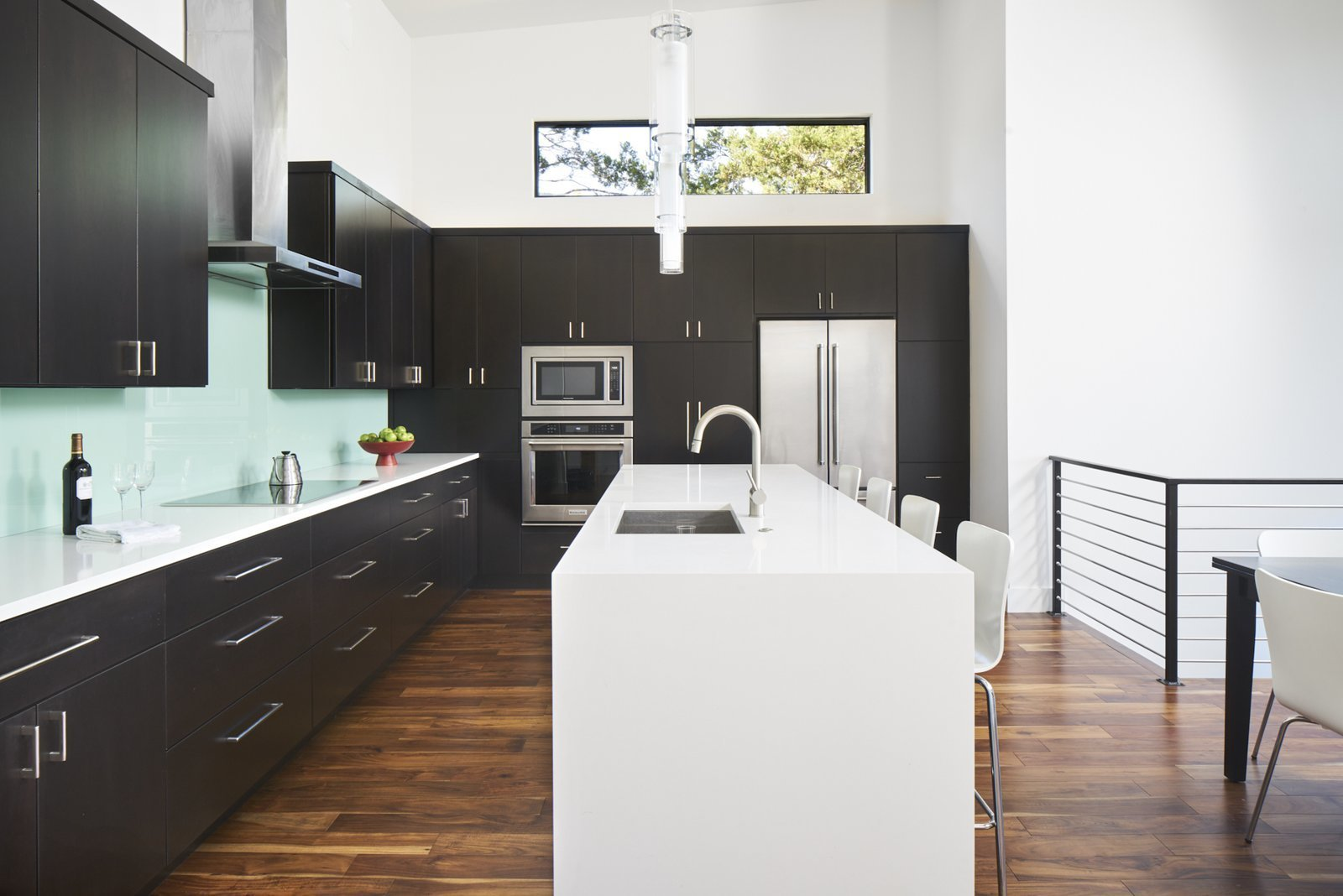 Kitchen, Undermount Sink, Wall Oven, Refrigerator, Microwave, Range Hood, Medium Hardwood Floor, Cooktops, and Pendant Lighting Cameron residence in Austin, Texas  Photo 5 of 7 in 6 Simple Ways to Save on Your Kitchen Renovation