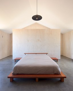 On the upper level of a timber home in Chile is a corridor with a studio, library, and gallery that leads to the ensuite master bedroom. In this understated space, a single, dramatic pendant light hangs, making use of an exposed bulb.