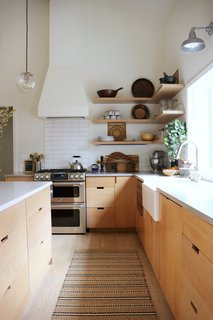 The team replaced all the cabinetry and fixtures, and located the kitchen sink directly in front of a large window.