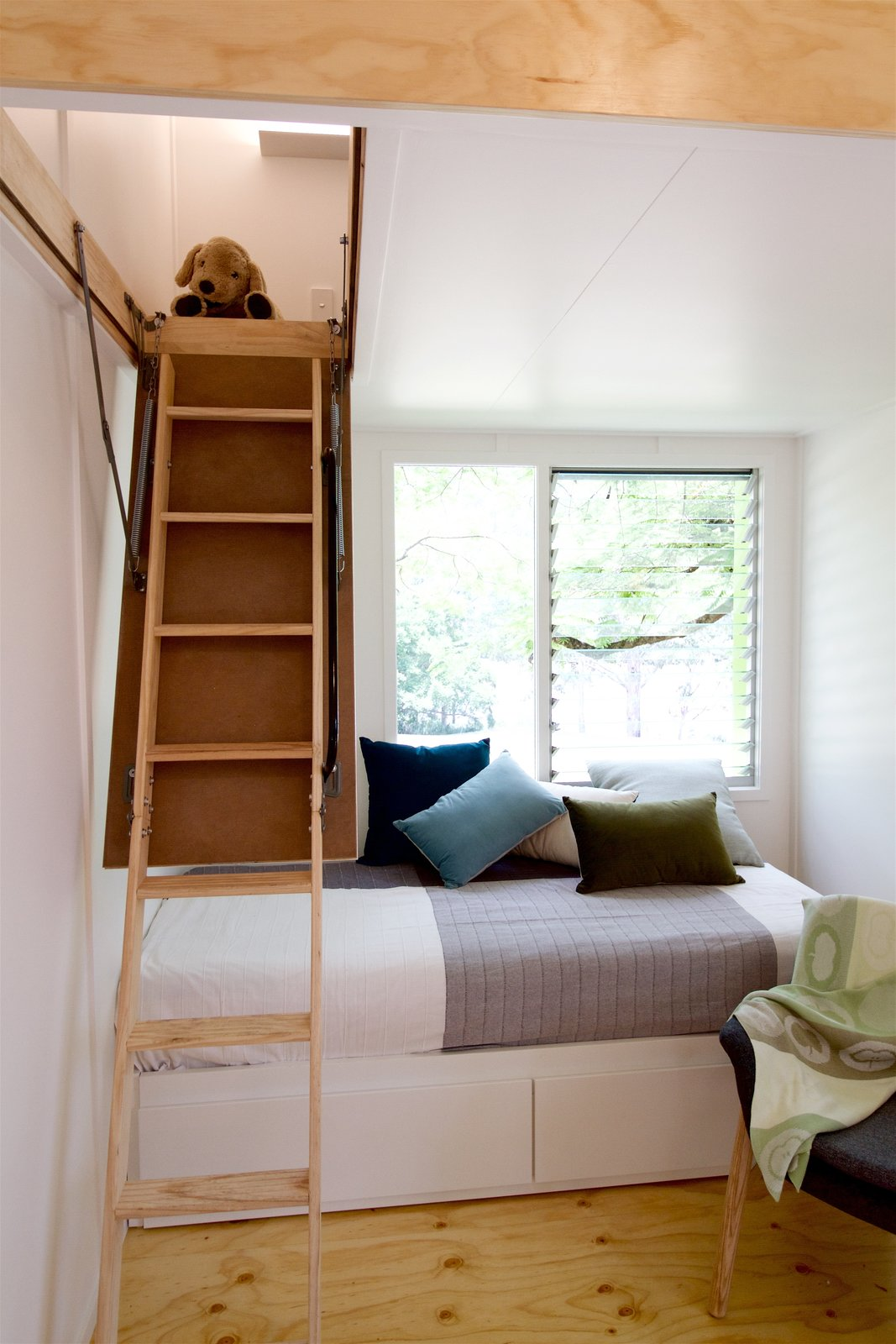 Staircase and Wood Tread A retractable ladder, and no built-in furniture or cabinetry in the main living area makes a range of layouts and arrangements possible.  Best Photos from This Midcentury-Inspired Tiny House Radiates Clever Design