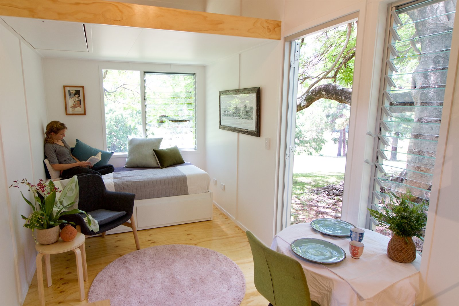Bedroom, Bed, Light Hardwood Floor, Rug Floor, and Chair The sleeping loft can be accessed with a convenient retractable ladder with multiple grab-points that disappears into the ceiling when not in use.  Best Photos from This Midcentury-Inspired Tiny House Radiates Clever Design
