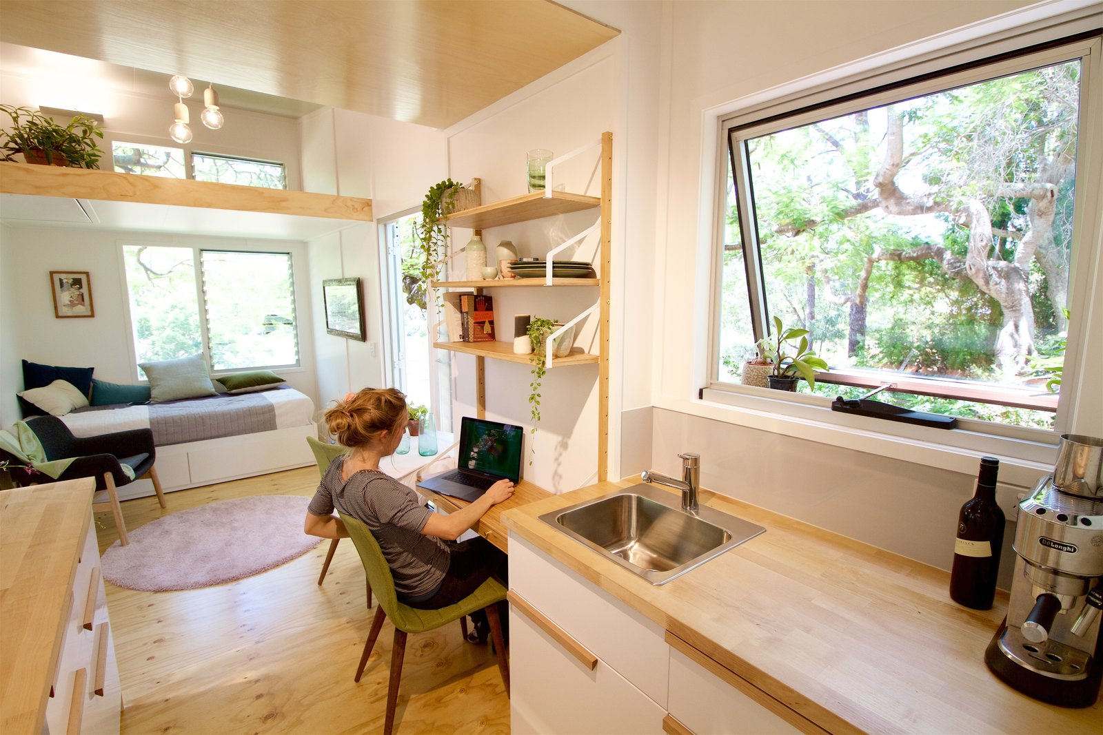 Office, Desk, Chair, Shelves, Light Hardwood Floor, and Bookcase The front door leads into a tall space where the ceiling rakes upwards toward a generous feature window.  Best Photos from This Midcentury-Inspired Tiny House Radiates Clever Design