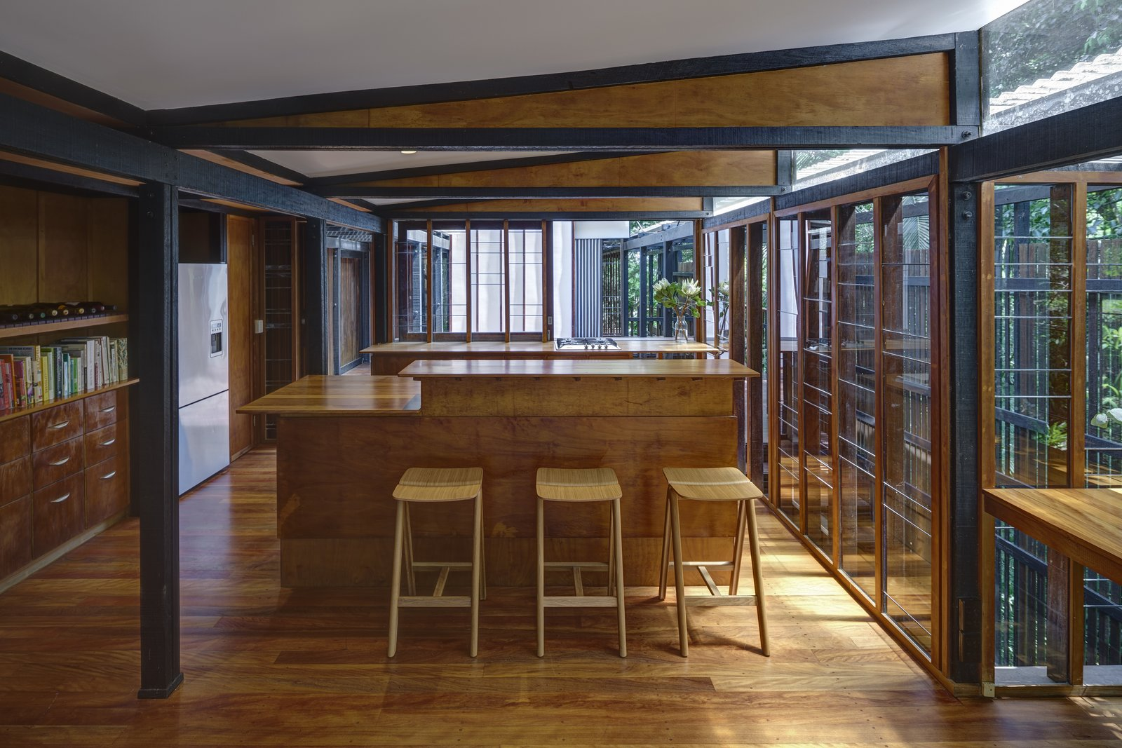 Kitchen, Wood, Medium Hardwood, Recessed, Refrigerator, Range, and Wood At the center of the house, on the upper level, is a kitchen and dining area fitted with glazed walls thst can be opened to connect with the outdoor decks, and green landscape.  Best Kitchen Medium Hardwood Wood Photos