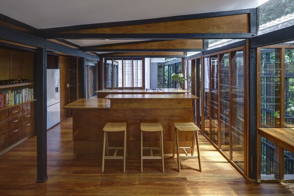 At the center of the house, on the upper level, is a kitchen and dining area fitted with glazed walls thst can be opened to connect with the outdoor decks, and green landscape.