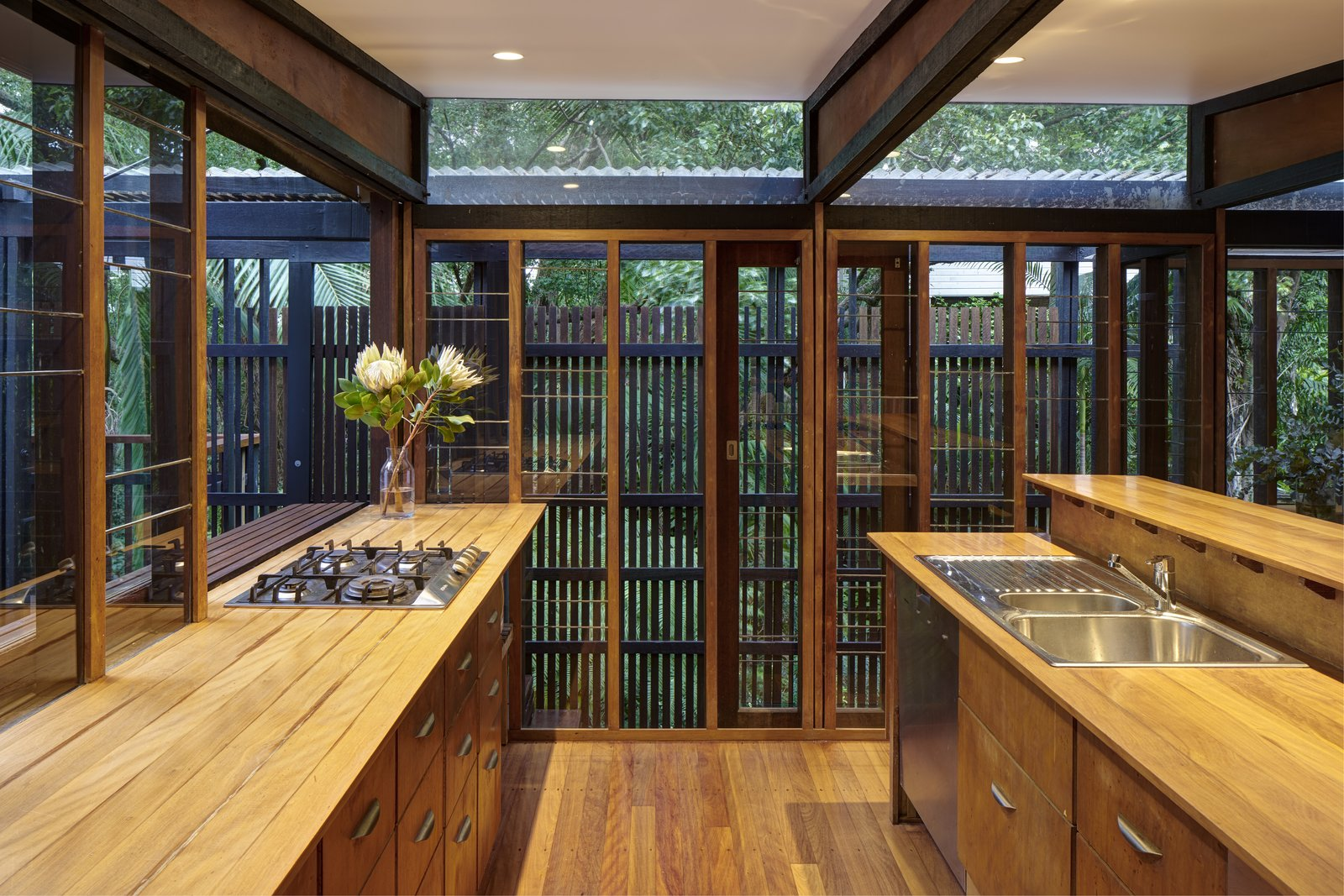 Kitchen, Wood, Drop In, Wood, Medium Hardwood, Dishwasher, Recessed, and Cooktops Within each pavilion are spaces for sleeping, bathing, working, eating, socializing, reading and contemplation.  Best Kitchen Medium Hardwood Wood Photos from This Brisbane Home For Sale Is a Lush Sanctuary