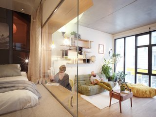 """""""With a single contribution of natural light -- the windowed facade facing street -- the apartment is designed to be 'turned' towards this light, with its glass rooms. Elements holding the old garage function were kept as witnesses and graphic structures of the apartment,"""" says Pelcé."""