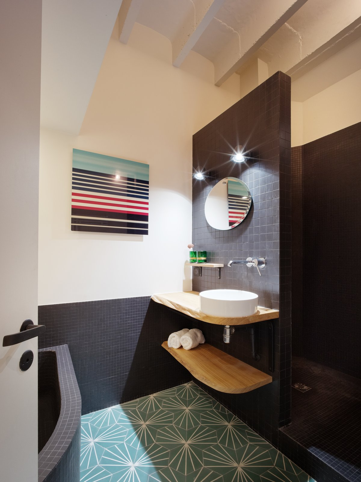 Bath, Wood, Mosaic Tile, Vessel, Drop In, Ceramic Tile, and Wall The simple bathroom was fitted with colored glass and black tiles, and accomodates a generous bathtub and shower.  Best Bath Wall Drop In Photos from This Compact Home in Paris Has Nearly 70 Concealed Closets