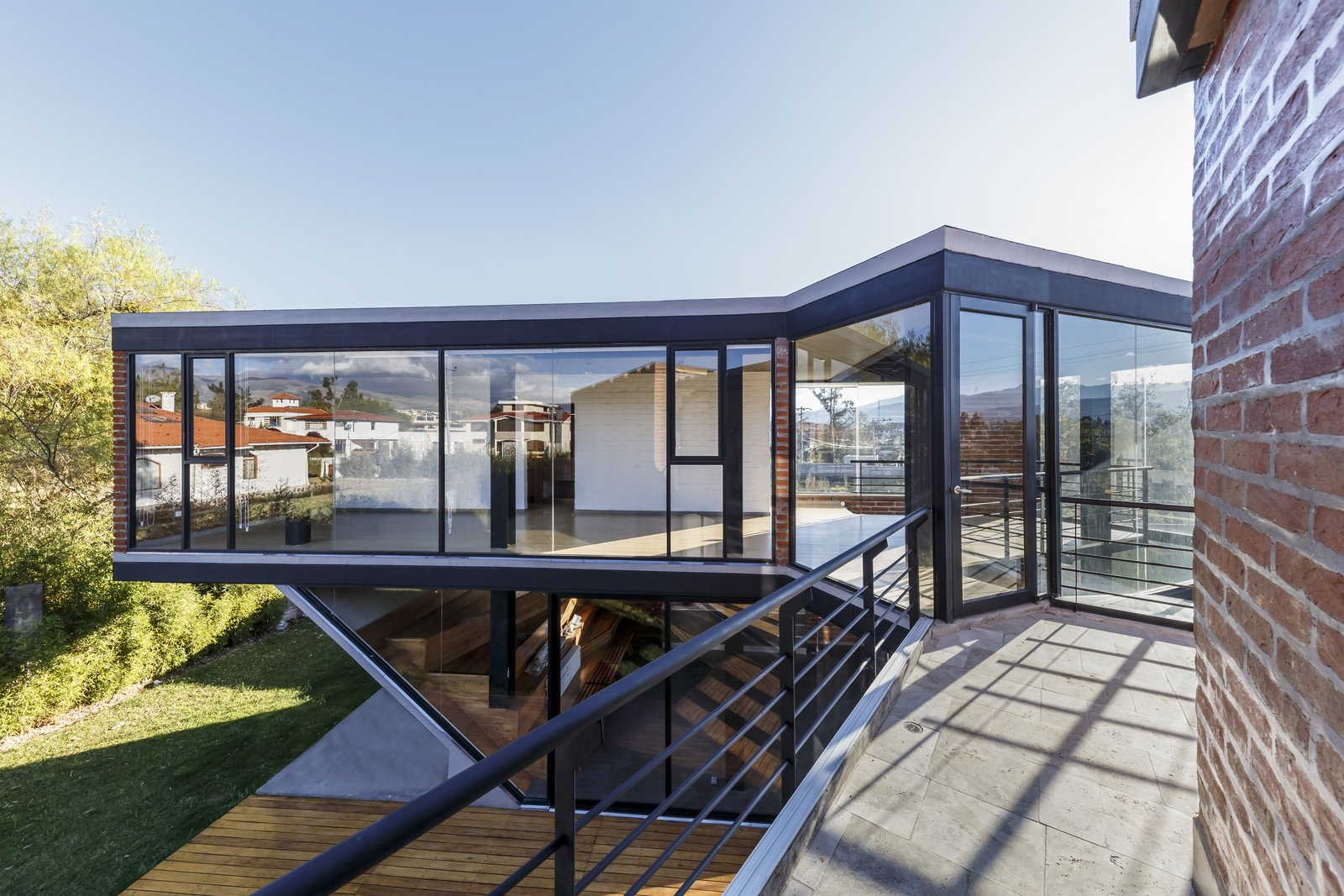 Exterior, Brick, Glass, House, Flat, and Wood The second C folds towards the interior, and takes in the morning sun.  Best Exterior Glass Brick Wood Photos from A Family Lives Harmoniously Together in This Captivating Multi-Generational Home