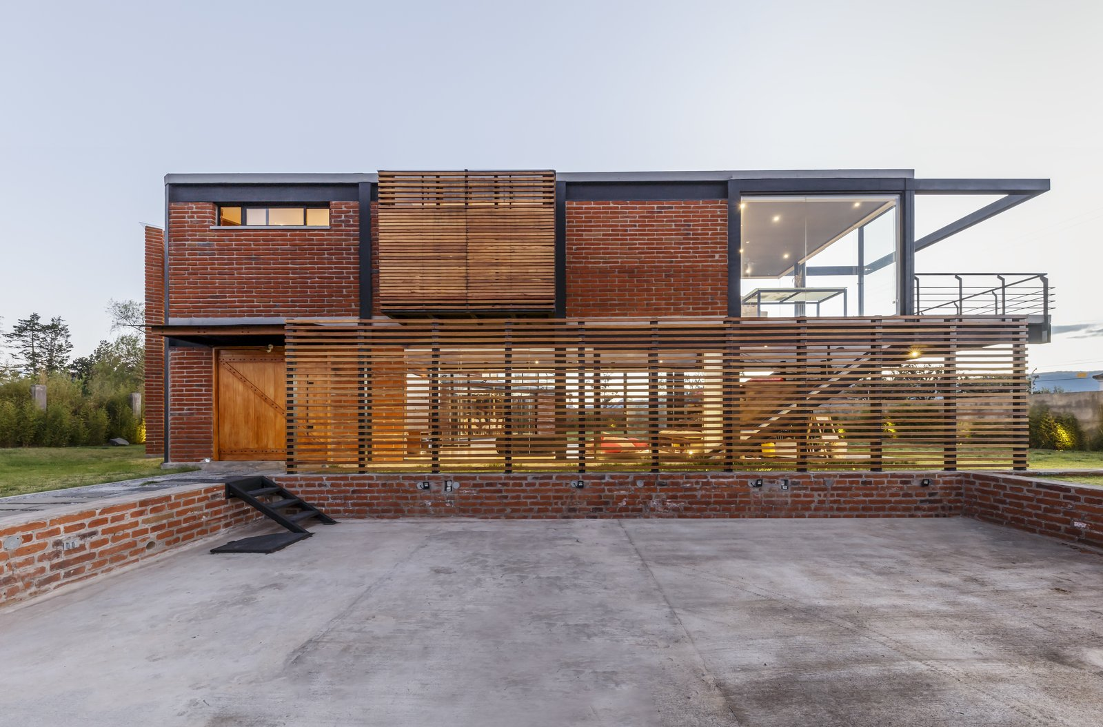 Exterior, Metal, Glass, House, Flat, Brick, and Wood A wooden screen provides privacy, and offers protection from the strong midday sun.  Best Exterior Glass Brick Wood Metal Photos from A Family Lives Harmoniously Together in This Captivating Multi-Generational Home