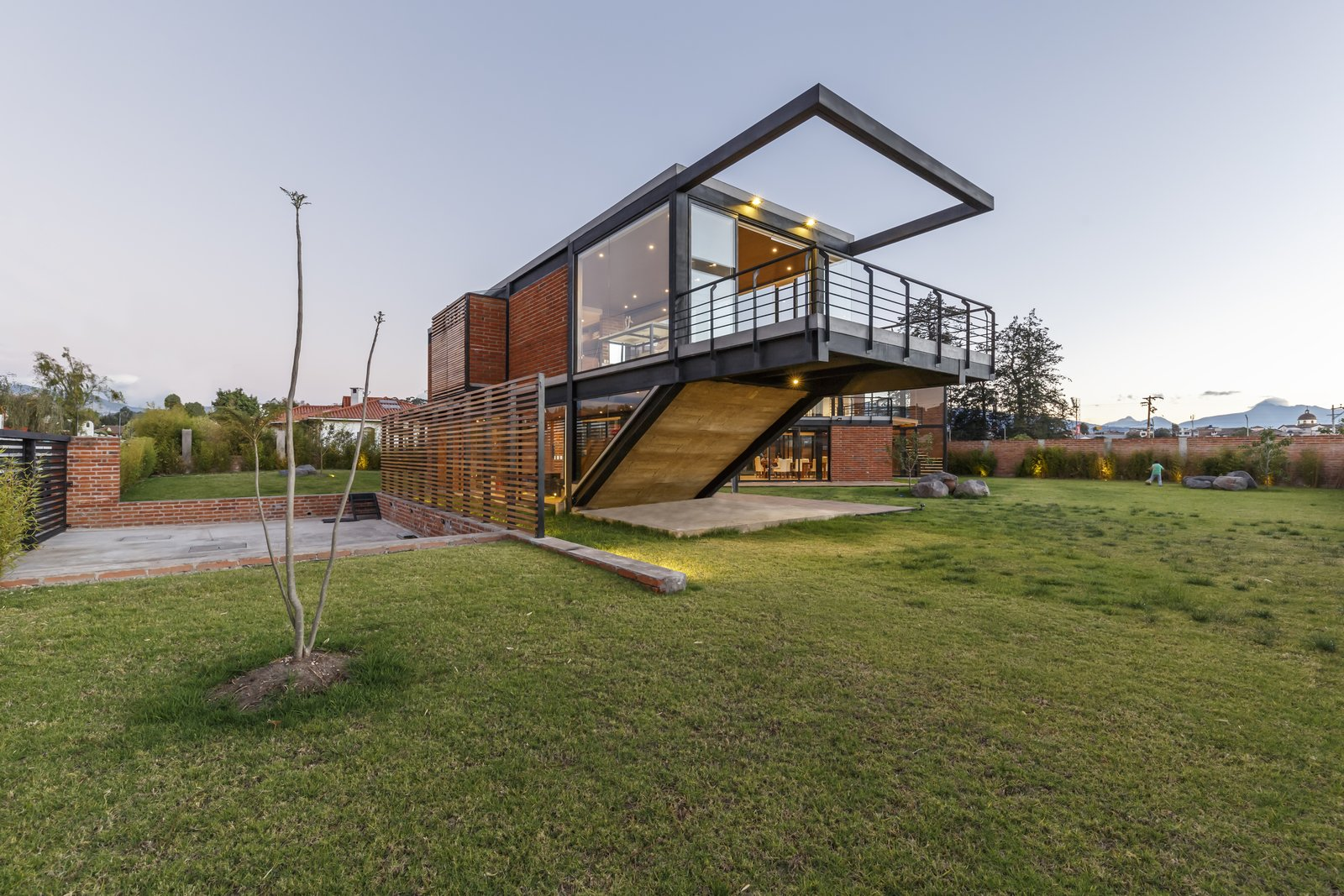 Exterior, Metal Roof Material, Brick Siding Material, House Building Type, Glass Siding Material, Flat RoofLine, and Wood Siding Material To enable the two families to live independently, and interdependently, Estudio A0 co-founder Ana María Durán Calisto came up with a 5,457-square-foot home that consists of two volumes, set in a Z formation.  Best Photos from A Family Lives Harmoniously Together in This Captivating Multi-Generational Home