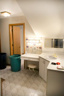 The original bathroom featured a tiny sink and vanity outside the door, as well as a hallway to connect the space to the master bedroom. To create a more spacious atmosphere, Bertolini closed off the hallway so the area could be converted into one large single room.