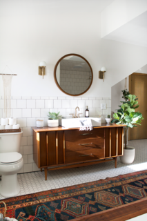 """She has always adored mixing old and new furniture, so she knew she wanted to find a vintage dresser to serve as the vanity. """"It took some time, but I eventually found the dresser at a local antique store that was the perfect size,"""" she explains. Once she found it, she had a vessel sink and a Delta faucet in champagne bronze incorporated. Another one of Bertolini's favorite vintage pieces is the rug from Swoon Rugs."""