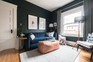She painted the walls a deep green—Salamander by Benjamin Moore—added a blue velvet pull-out couch, new artwork, new furniture, and picture rail molding.