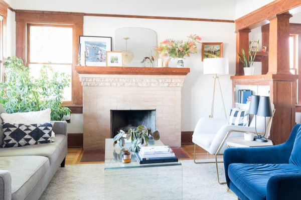 """""""After restoring the interiors, I layered the spaces with art and unique paint colors or decor elements to make it uniquely ours,"""" she says. The living room got new floors, drywall, refinished bookcases, and furniture."""