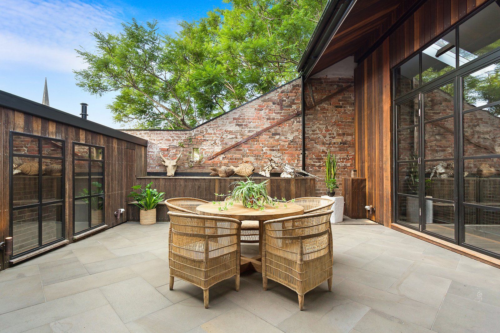 Outdoor, Large Patio, Porch, Deck, Rooftop, and Wood Fences, Wall Polished concrete and exposed bricks give the home an industrial look.  Photo 12 of 12 in The Glowing Converted Warehouse of Painter Fred Cress Is Open For Bids