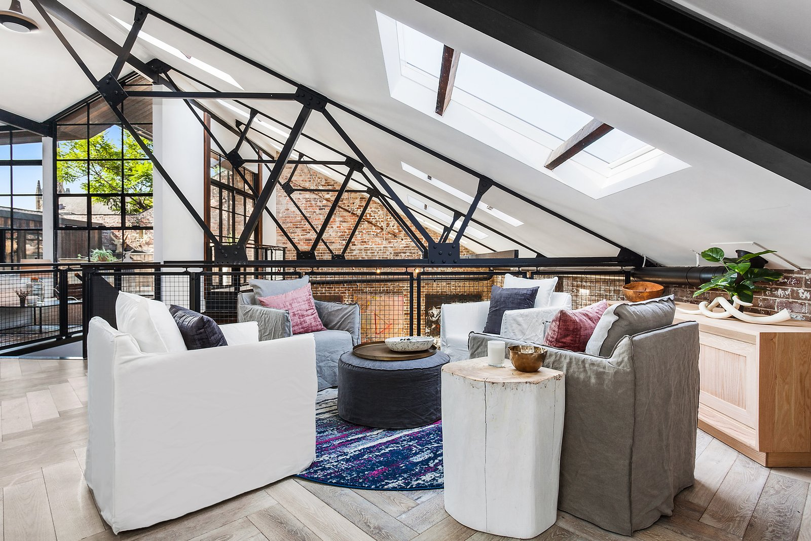 Living Room, Coffee Tables, End Tables, Console Tables, Chair, Light Hardwood Floor, and Rug Floor The soaring ceilings are interlaced with timber trusses and exposed steel.  Photo 4 of 12 in The Glowing Converted Warehouse of Painter Fred Cress Is Open For Bids