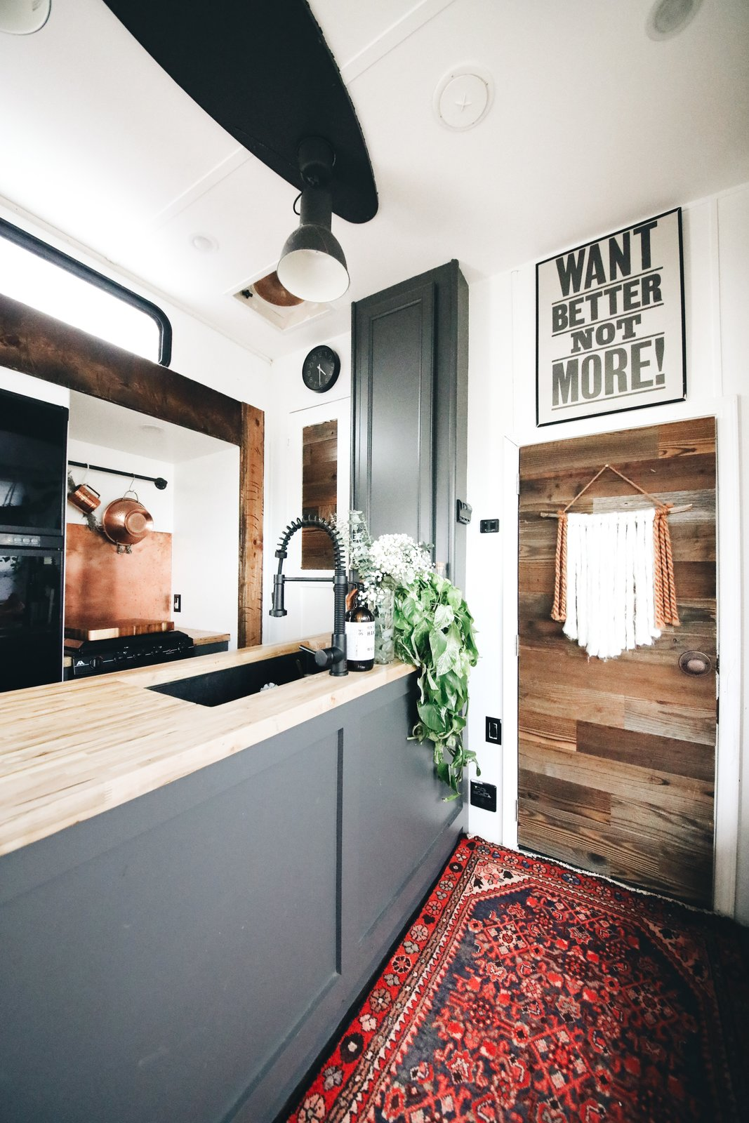 """Kitchen, Ceiling Lighting, Rug Floor, Wood Counter, and Undermount Sink """"I wanted a blank slate that was versatile so I could switch it up, and change things around as we all grew in our tiny space,"""" she says  Photos from A Couple Transform a Toy Hauler Into a Mobile Tiny Home For $6K"""