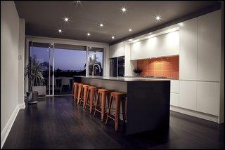 An eye-catching, red-tiled backsplash enlivens this kitchen.