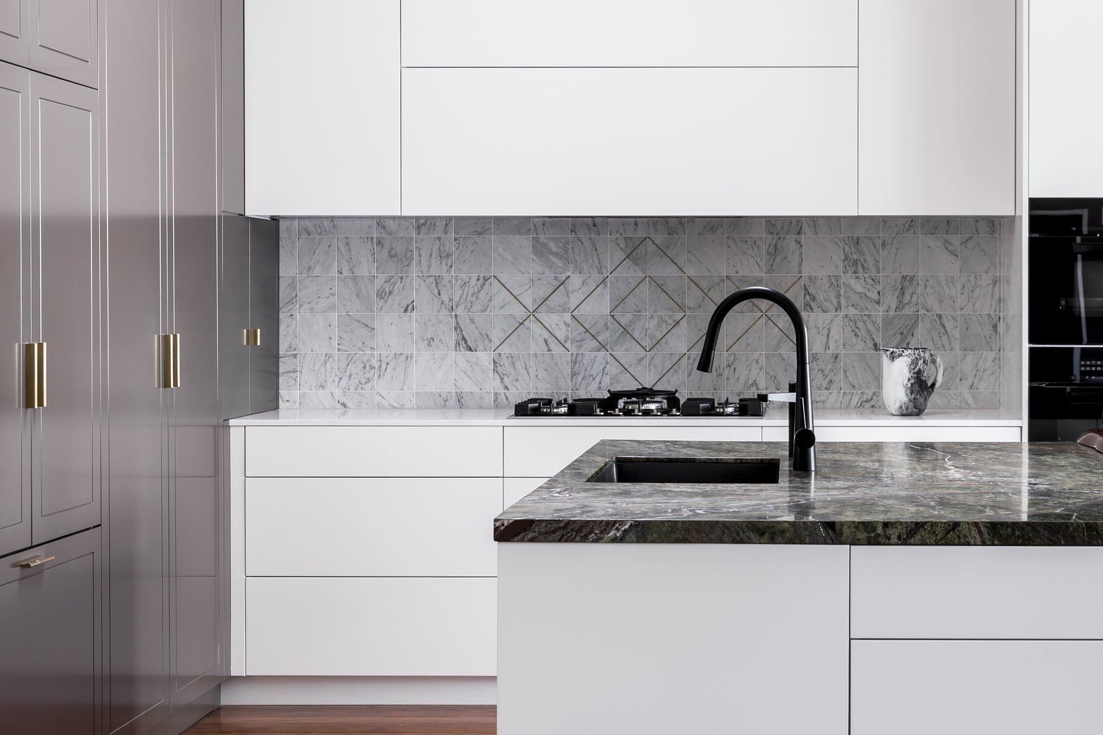 """Kitchen, Dark Hardwood Floor, Undermount Sink, Wall Oven, White Cabinet, and Cooktops This """"Drummoyne kitchen"""" was designed by Laura Poilly for Blue Tea Kitchens.    Photo 8 of 11 in 10 Design Tips for Kitchens, According to Expert Renovators"""
