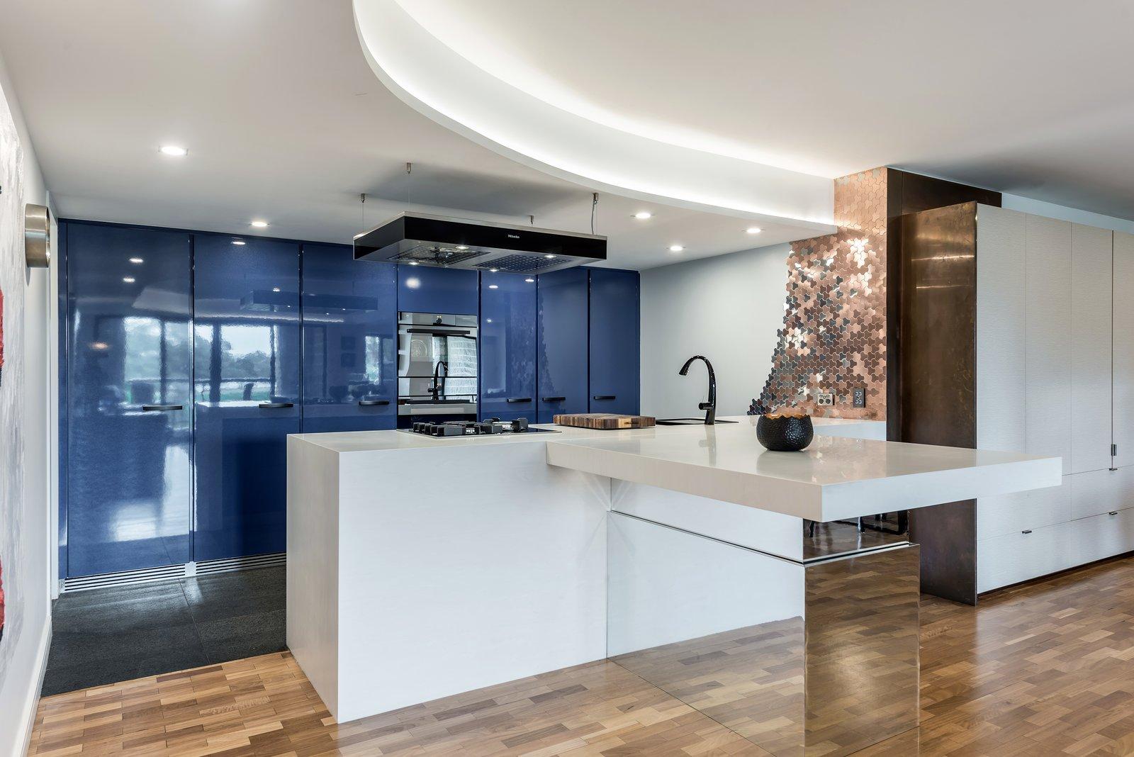 Kitchen, Medium Hardwood Floor, Cooktops, Range Hood, White Cabinet, Drop In