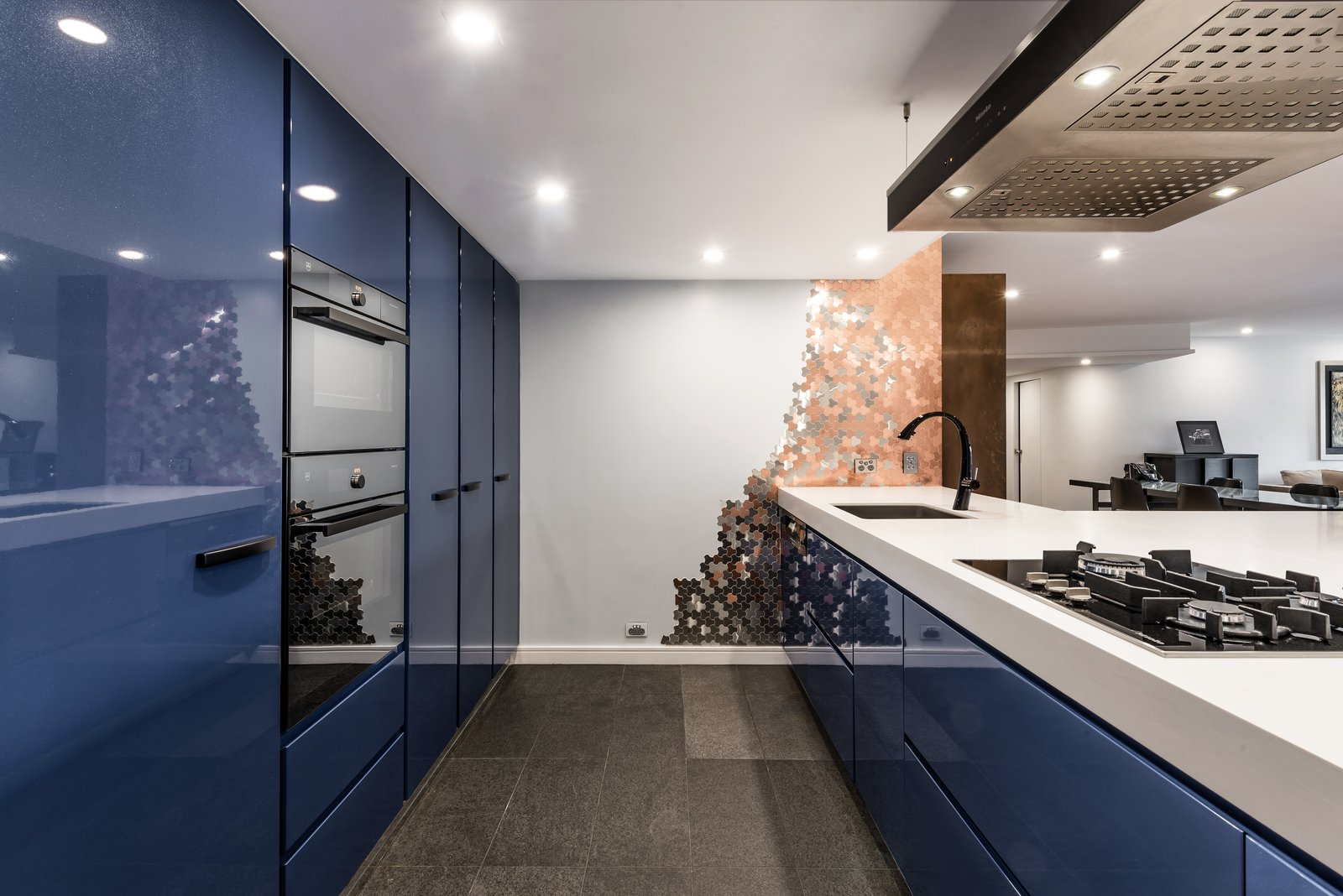 """Kitchen, Colorful Cabinet, Cooktops, Undermount Sink, Wall Oven, and Recessed Lighting This """"Blue kitchen"""" was designed by Marianne Gailer.    Photo 4 of 11 in 10 Design Tips for Kitchens, According to Expert Renovators"""