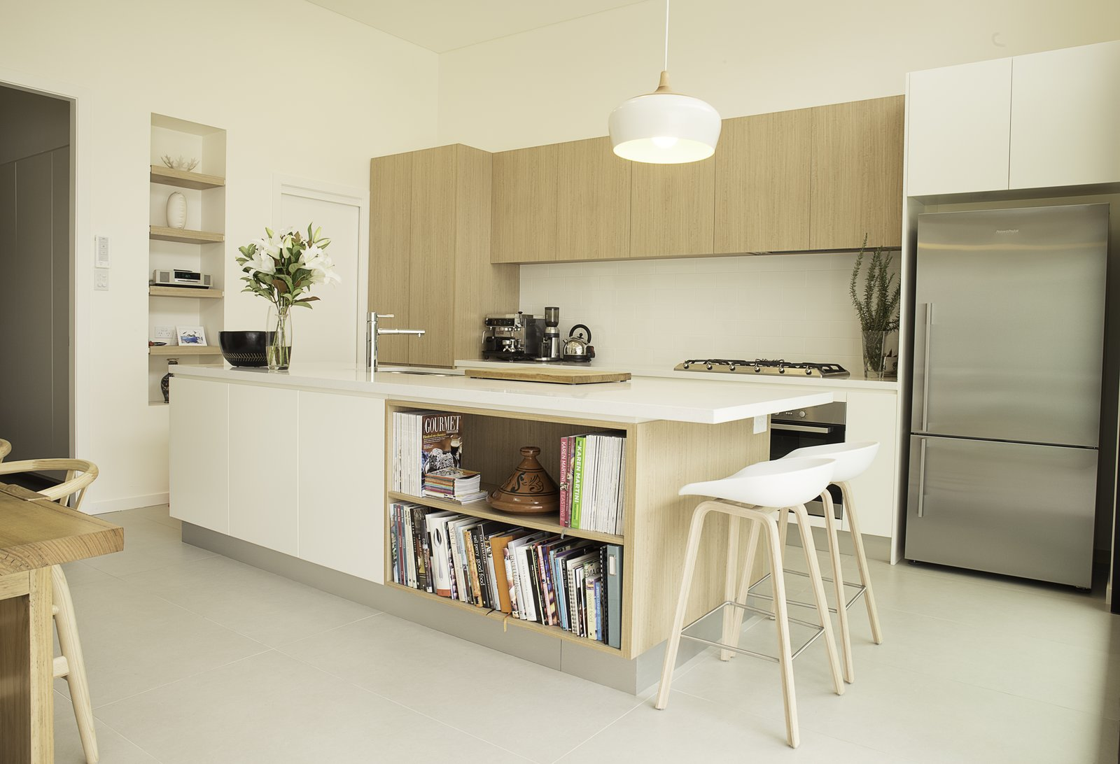 """Kitchen, White Cabinet, Undermount Sink, Refrigerator, Wood Cabinet, Pendant Lighting, Wall Oven, and Cooktops This """"Coogee kitchen"""" was designed by Nadia Hursky for Blue Tea Kitchens.    Photo 9 of 11 in 10 Design Tips for Kitchens, According to Expert Renovators"""