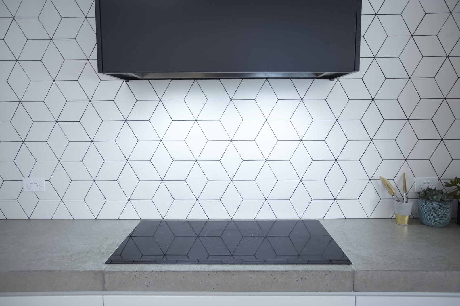 Kitchen, Range Hood, Ceramic Tile Backsplashe, Cooktops, and Concrete Counter You can use your new backsplash to add texture and visual flair to the space.    Photo 6 of 11 in 10 Design Tips for Kitchens, According to Expert Renovators