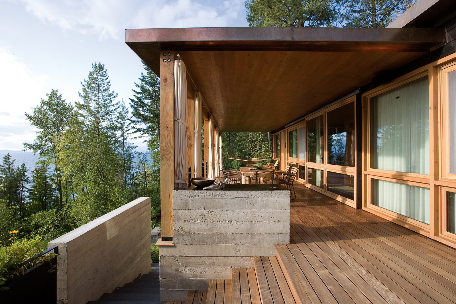 Outdoor, Trees, Concrete, Large, Wood, Wood, and Side Yard The floors and decking are all made from long-lasting, rot-resistant ipe wood.  Best Outdoor Concrete Wood Photos from Stacked-Wood Walls Tie This Eco-Friendly Camp to the Montana Landscape