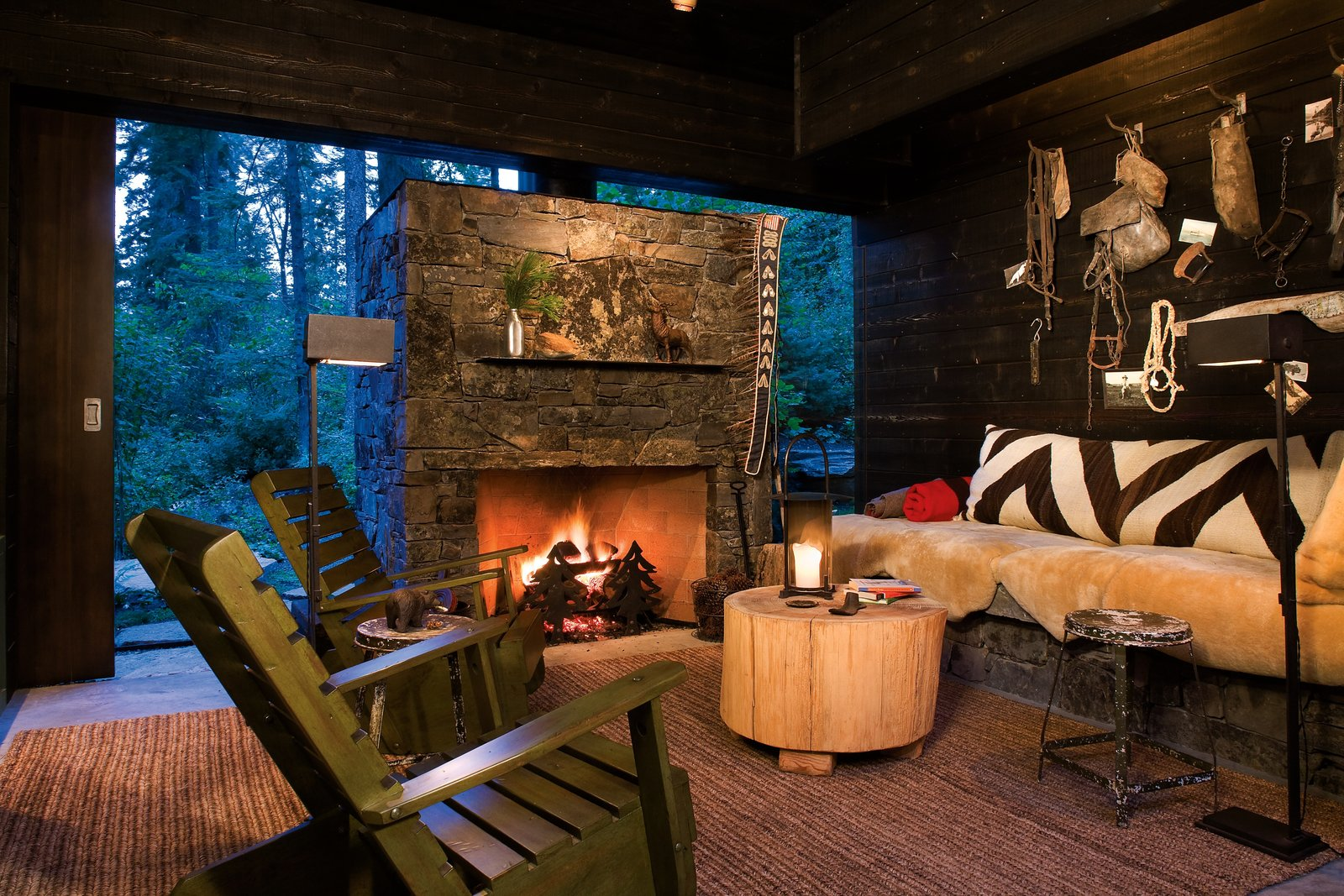 Living Room, Standard Layout Fireplace, Coffee Tables, Wood Burning Fireplace, Sofa, Chair, Floor Lighting, and Rug Floor The interiors have a cabin-like feel.  Photo 7 of 14 in Stacked-Wood Walls Tie This Eco-Friendly Camp to the Montana Landscape
