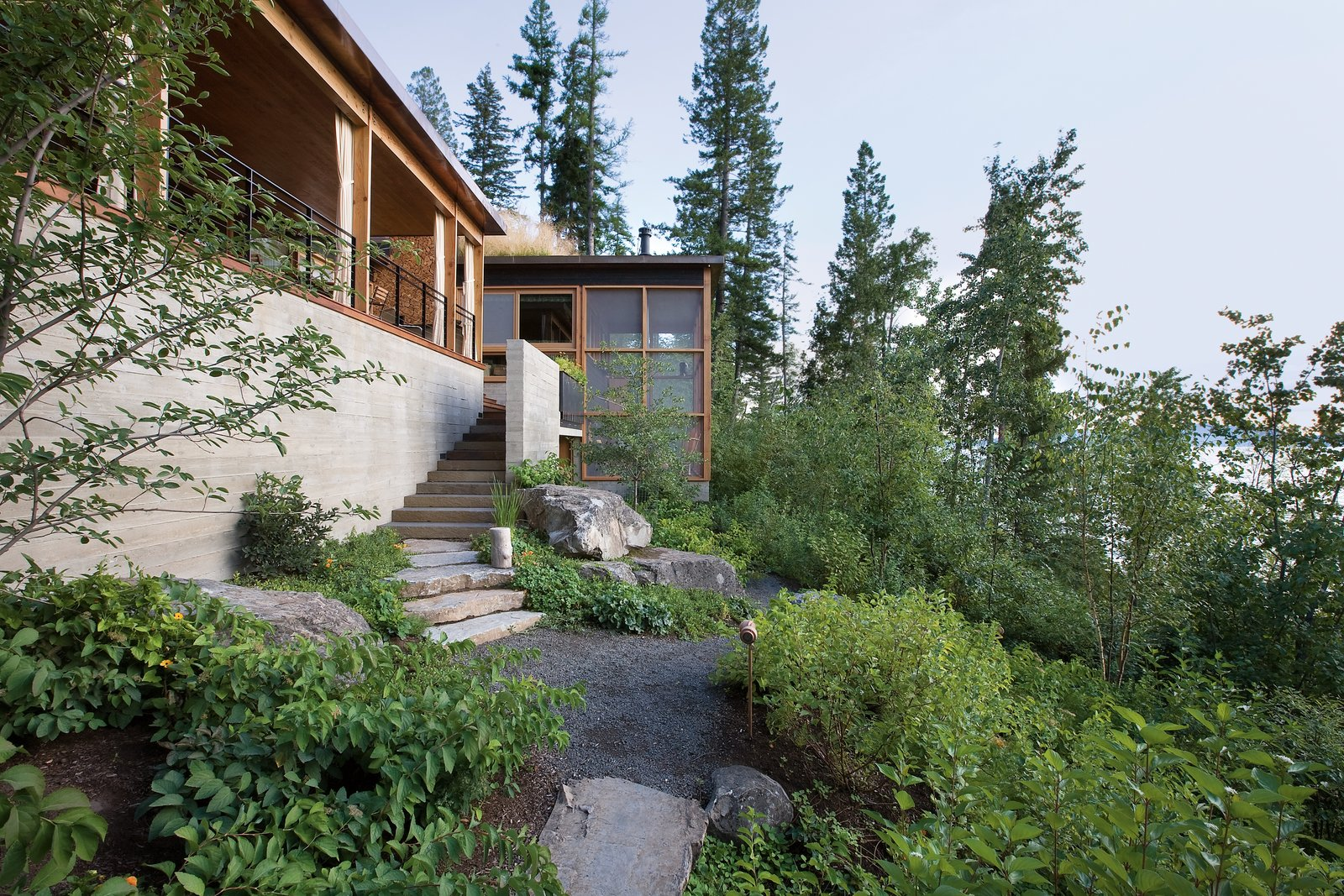 Outdoor, Shrubs, Walkways, Boulders, Gardens, and Front Yard Each of the buildings provides cozy, cave-like spaces with generous, sun-lit porches that look out to stunning views.  Photo 5 of 14 in Stacked-Wood Walls Tie This Eco-Friendly Camp to the Montana Landscape