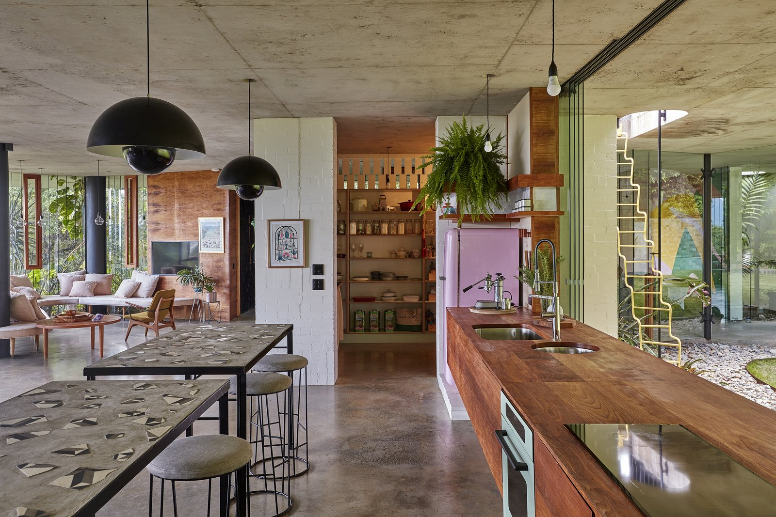 Kitchen, Cooktops, Concrete, Pendant, Wall Oven, Wood, and Undermount Between the common areas and the master bedroom is a timber wall with a bookshelf on one side.  Best Kitchen Concrete Undermount Wood Photos from A Funky, Curvaceous Rainforest Home in Australia Hits the Market