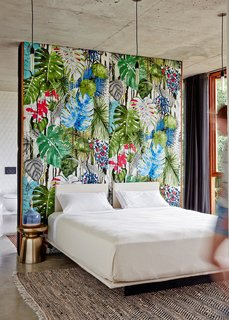 The wall in the master bedroom is upholstered in tropical print fabric by Christian Lacroix.