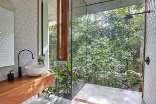 An open, glass-encased shower gives the homeowners the sensation of bathing outdoors.