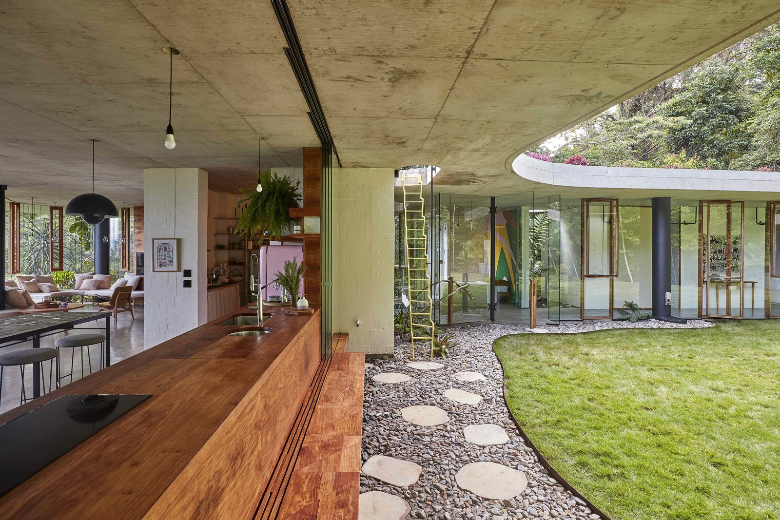 Kitchen, Wood, Undermount, Cooktops, Concrete, and Pendant A rosewood bench in the kitchen folds to form an outdoor seat.  Best Kitchen Concrete Undermount Wood Photos from A Funky, Curvaceous Rainforest Home in Australia Hits the Market