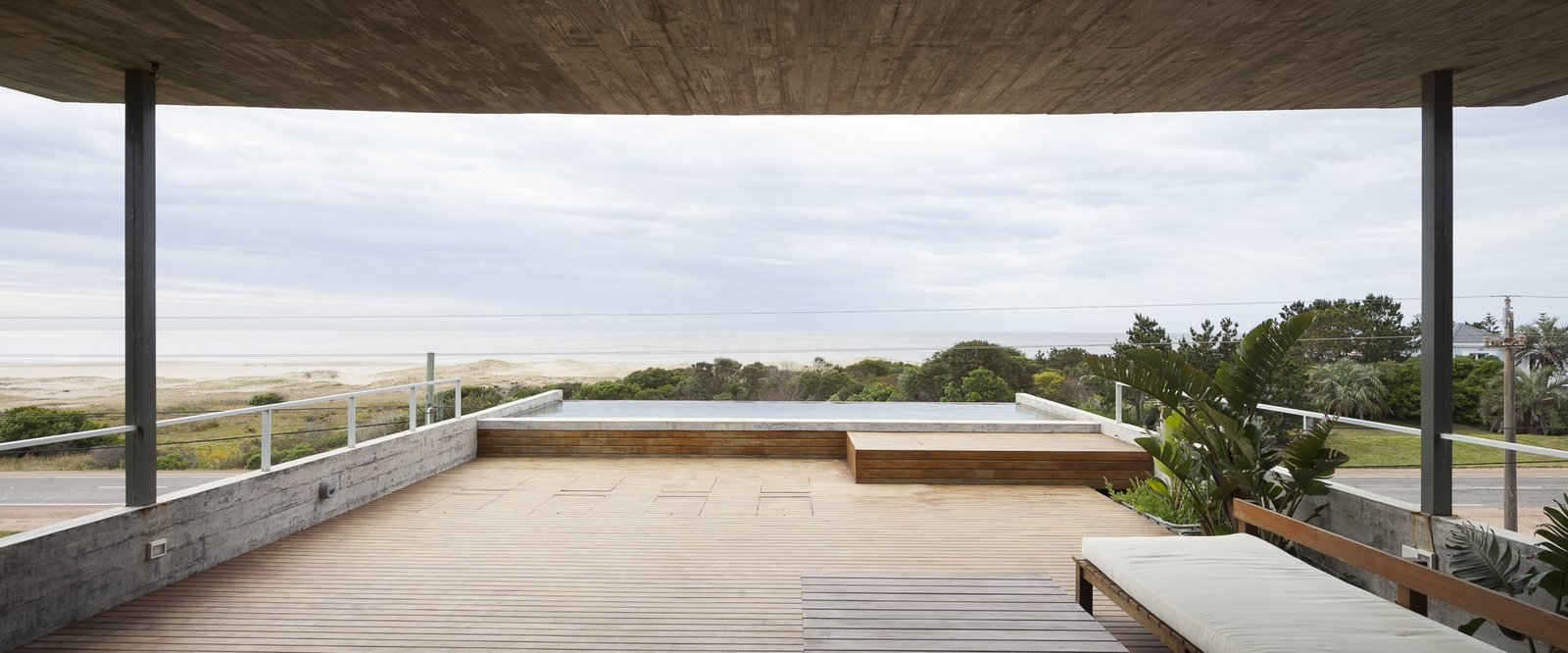 Outdoor, Large, Decking, Large, Wood, Infinity, and Concrete The third level can be totally opened up to fuse indoor and outdoor space.  Best Outdoor Decking Large Photos from A Concrete Abode in Uruguay Embraces its Beachfront Setting