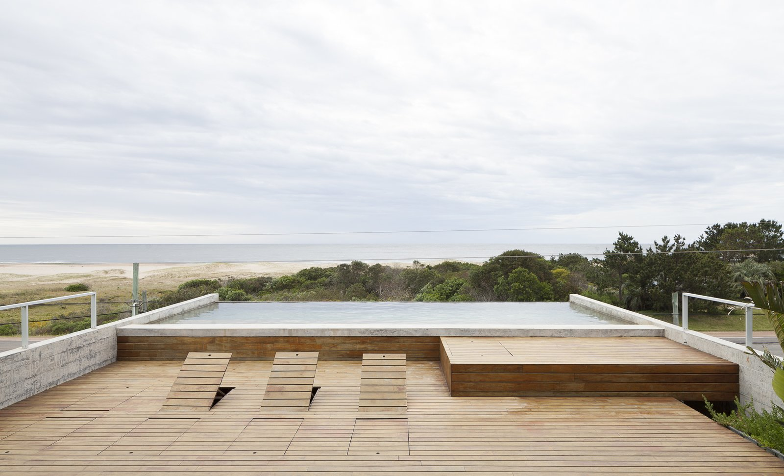 Outdoor, Large Patio, Porch, Deck, Large Pools, Tubs, Shower, Wood Patio, Porch, Deck, Decking Patio, Porch, Deck, Concrete Fences, Wall, and Infinity Pools, Tubs, Shower The deck rises up in sections to become sun loungers.  Photo 11 of 12 in A Concrete Abode in Uruguay Embraces its Beachfront Setting