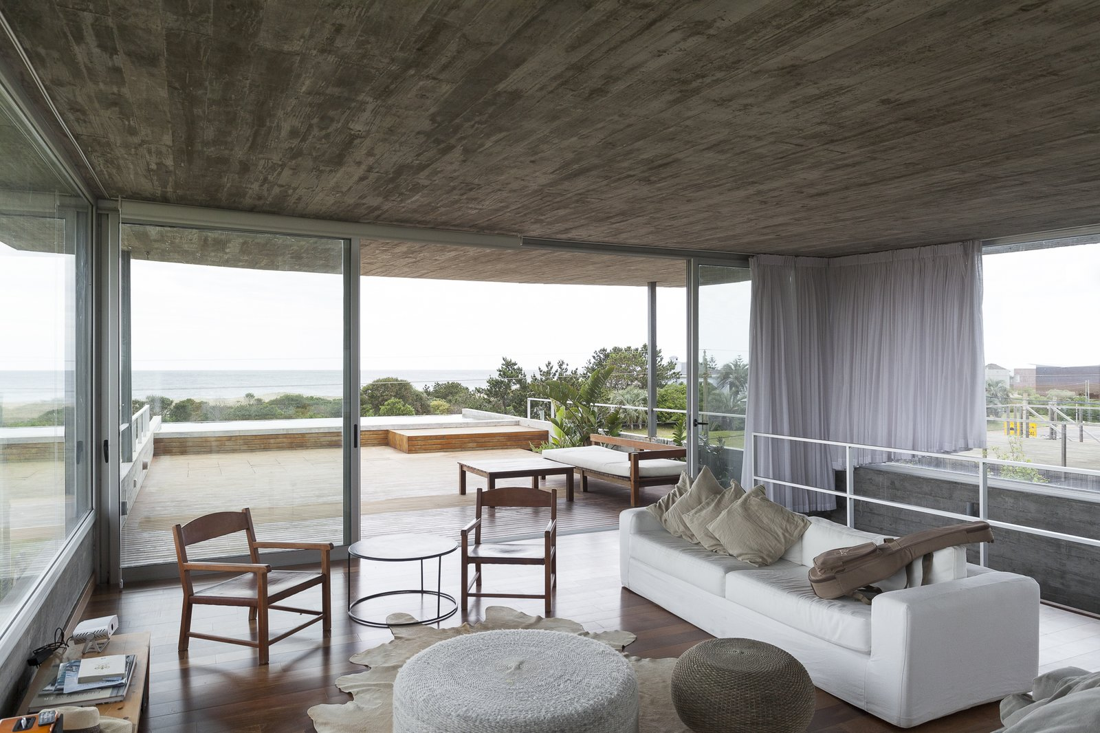 Living Room, End Tables, Console Tables, Ottomans, Chair, Sofa, Medium Hardwood Floor, and Rug Floor A triple-height staircase serves as the backbone of the house, connecting the various interior living spaces and promoting efficient circulation.  Photo 8 of 12 in A Concrete Abode in Uruguay Embraces its Beachfront Setting