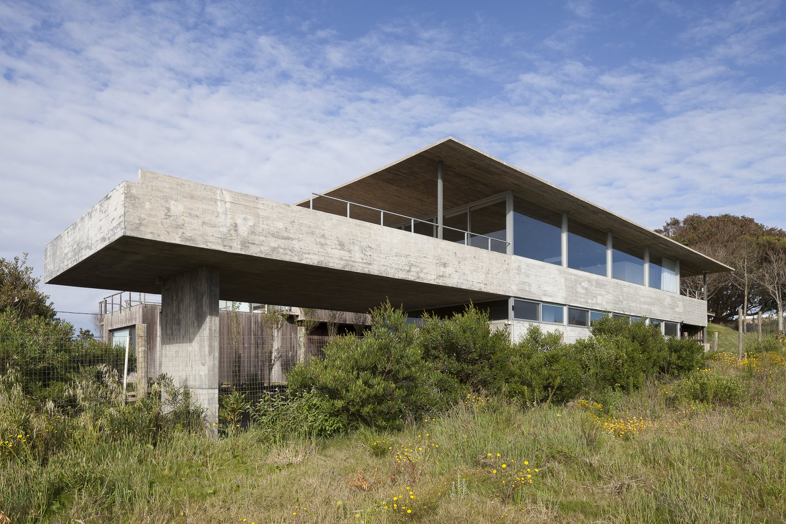Exterior, Concrete Siding Material, House Building Type, Beach House Building Type, and Flat RoofLine The house is split into three levels.  Photo 1 of 12 in A Concrete Abode in Uruguay Embraces its Beachfront Setting