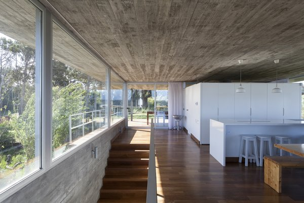 On one end of the top floor communal space, is a white volume, which neatly contains the kitchen, pantry, and toilet.