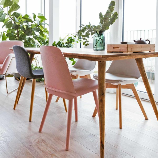 An up-close look at the dining table from Maisons du Monde, a pink dining chair from Habitat, and a black dining chair from Muuto.