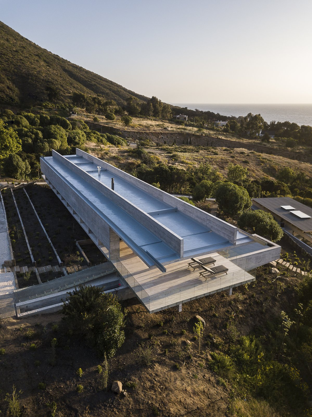 Exterior, Concrete Siding Material, House Building Type, and Flat RoofLine An aerial view of the clean-lined, futuristic home.  Photo 4 of 14 in This Chilean Concrete Home Levitates Off a Coastal Slope