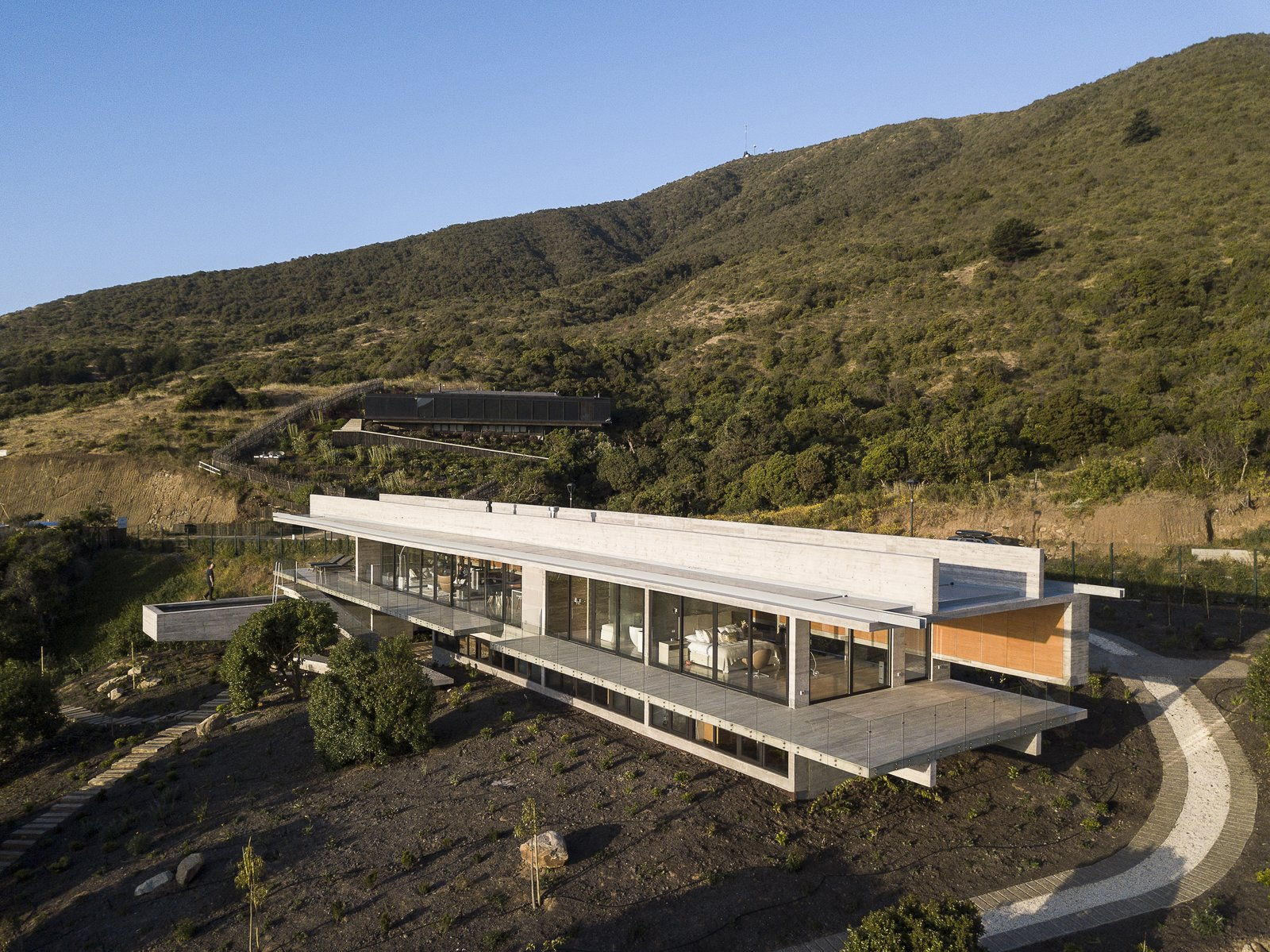 Exterior, Flat RoofLine, Concrete Siding Material, and House Building Type A staircase and a ramp rise where the transverse structures meet the pool volume.       Photo 3 of 14 in This Chilean Concrete Home Levitates Off a Coastal Slope
