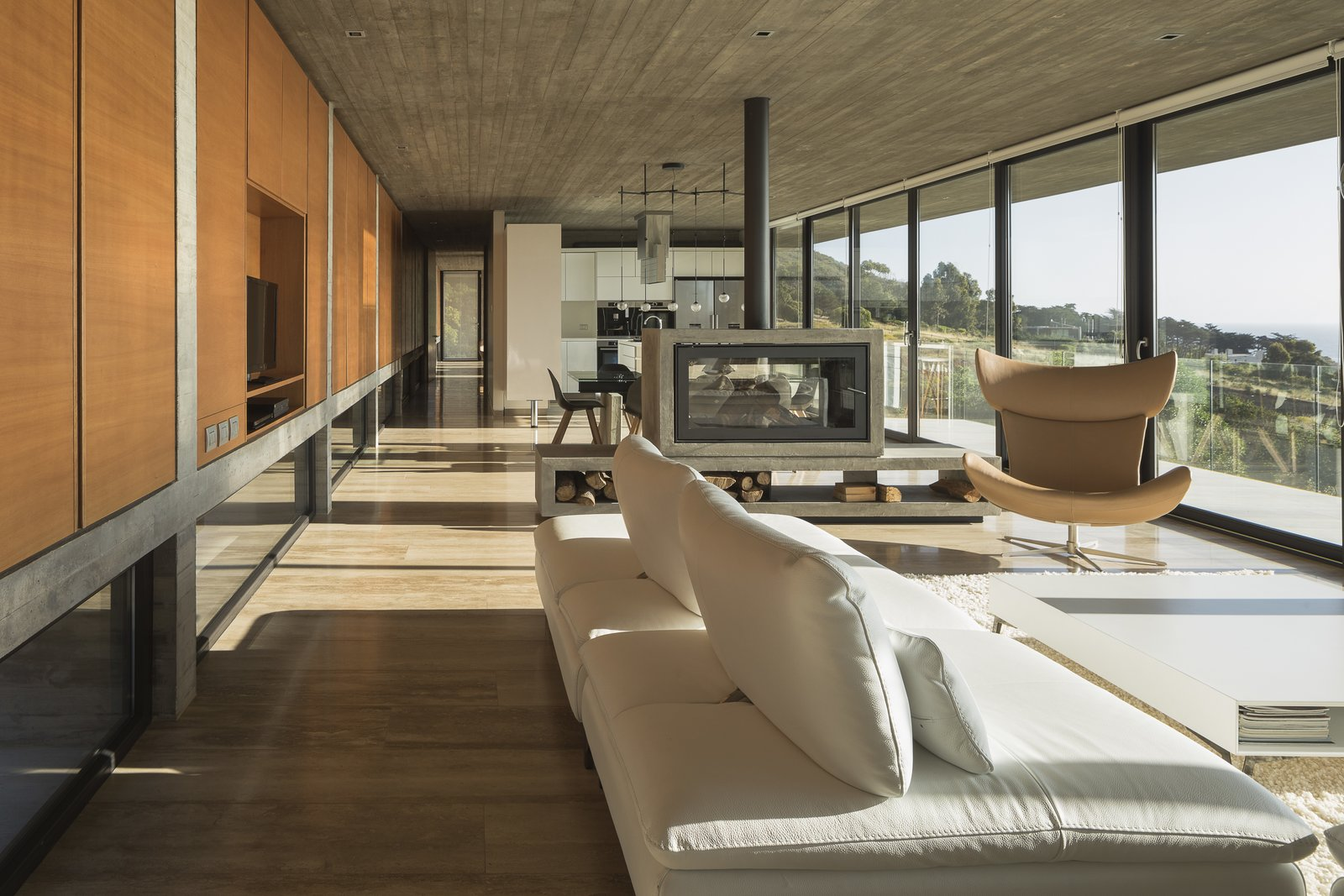 Living Room, Coffee Tables, Two-Sided Fireplace, Sofa, Chair, Recessed Lighting, and Rug Floor In the living areas, the inner surface of the massive beam-wall that frames the eastern façade is clad in wood, which adds a sense of warmth to counteract the coolness of the concrete.    Photo 7 of 14 in This Chilean Concrete Home Levitates Off a Coastal Slope