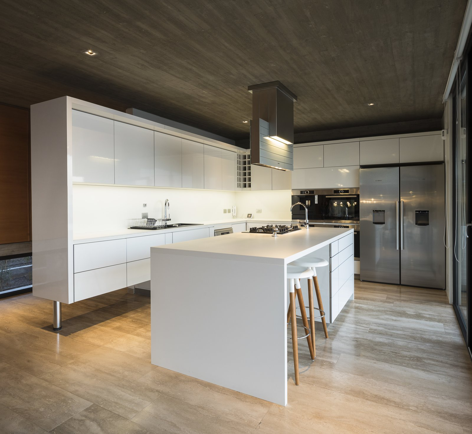 Kitchen, Wall Oven, Range Hood, Recessed Lighting, Ice Maker, Refrigerator, Cooktops, White Cabinet, and Drop In Sink An all-white kitchen works well with the concrete to give the space a cool, minimalist look.    Best Photos from This Chilean Concrete Home Levitates Off a Coastal Slope