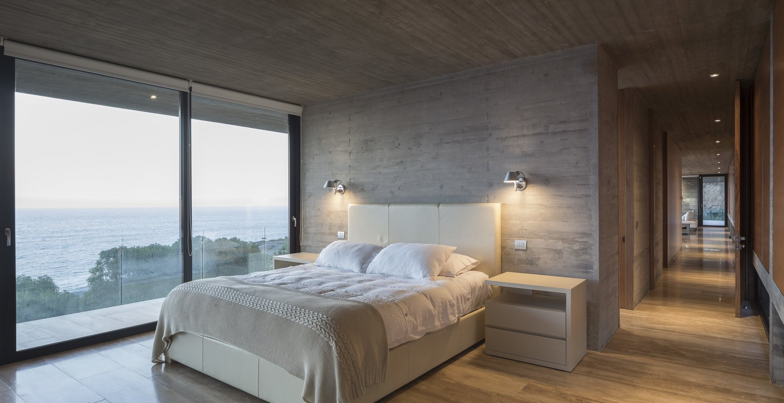 Bedroom, Night Stands, Bed, and Wall Lighting The master bedroom with an ensuite bathroom is also located on the access level.    Photo 9 of 14 in This Chilean Concrete Home Levitates Off a Coastal Slope