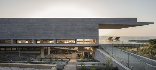 "The concrete beams support four walls, while also extending beyond to create massive, 23-foot-long cantilevers at both ends of the structure. As a result, the profile of the home looks like the letter ""H"" in the horizontal position, levitating on a slope."